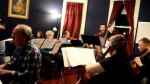 open rehearsal string ensemble with piano